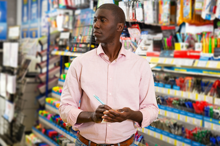 Portrait of male customer choosing new pen in stationery store Stockfoto