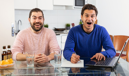 Men discuss and sign apartment sale contract agreement at home