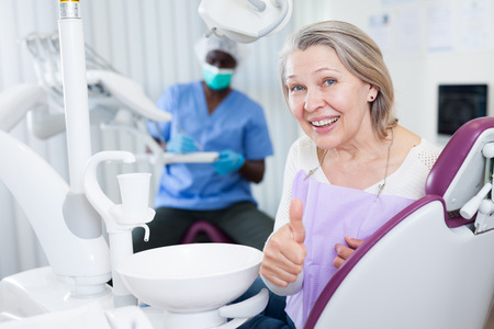 Happy cute mature woman sitting in dental chair after teeth cure giving thumb up 免版税图像