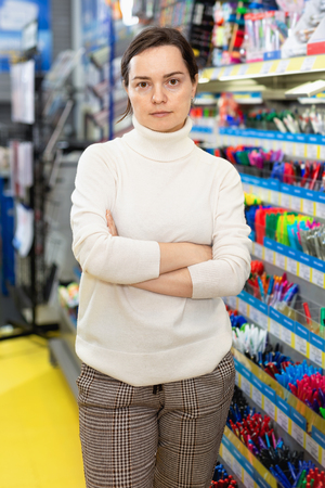 Portrait of happy cheerful  woman choosing ball pen at stationery store