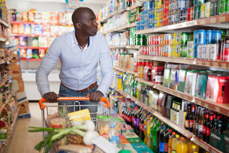 Portrait of young African male with grocery cart buying food products in supermarket Imagens