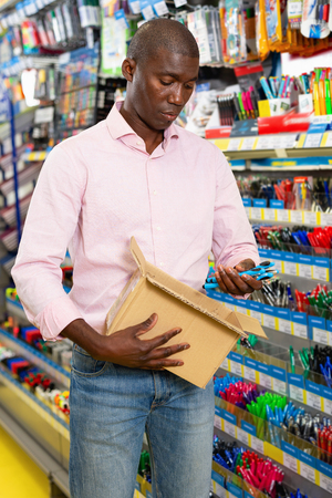 Cheerful positive smiling African American man choosing office supplies at stationery department of supermarket