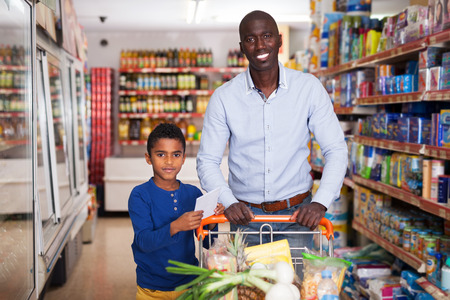 Portrait of friendly African American father and son with purchases during family shopping in store
