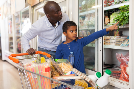 Friendly African-American family of father and tween child making purchases in supermarket, looking for fresh vegetables