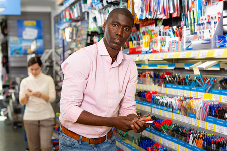Portrait of smiling Afro American man choosing ball pen at stationery store