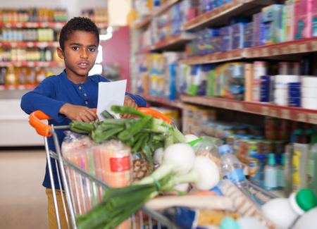 Smiling African American tween boy carrying purchases in trolley during shopping in grocery store