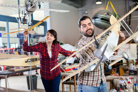 Positive smiling team of aircraft enthusiasts holding sports airplane models in workshop Foto de archivo