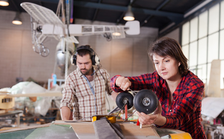 Female aircraft enthusiast engaged in creating plane models in workshop