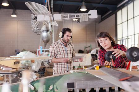 Positive couple enjoying their hobbies - modeling light airplanes in aircraft hangar