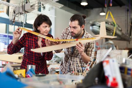 Amateus femenino y masculino dedicado a modelar modelos de aviones en el hangar de aviones. Centrarse en el hombre Foto de archivo