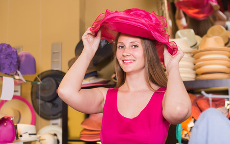 Young happy  woman choose straw hat in shop