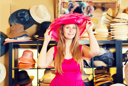 young cheeful  blonde female try on pink dress hat in botique