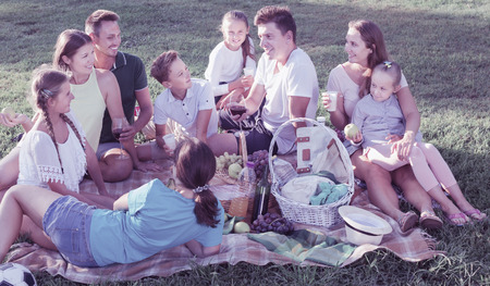 Group of glad people with kids enjoying picnic on green meadow together