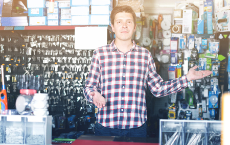 Portrait of adult employee selling and manufacturing keys in hardware store Imagens