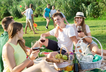 Happy parents enjoying picnic in nature, while children playing active games