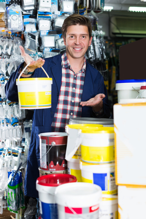Young happy worker selling tins of paint in hardware shop