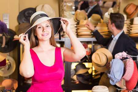 adult smiling woman try on hatinator hat  in shopping mall