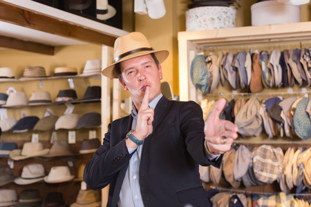portret of smiling young spanish guy try on panama at headwear store