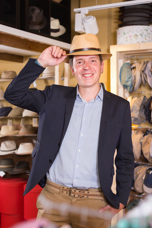 portret of happy european young guy try on panama at headwear store Stock Photo