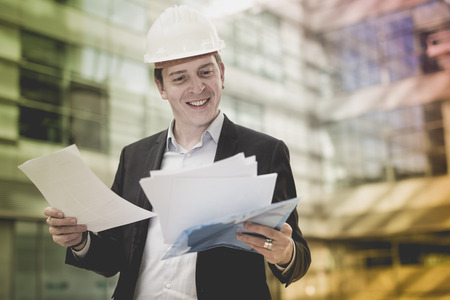Professional man in jacket and helmet working with documents