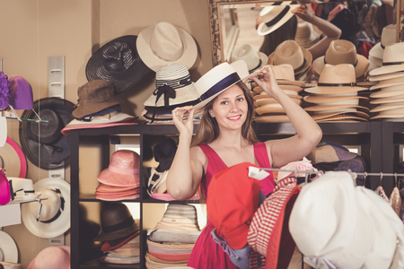 adult smiling girl try on floppy hat from the range in store Stock Photo