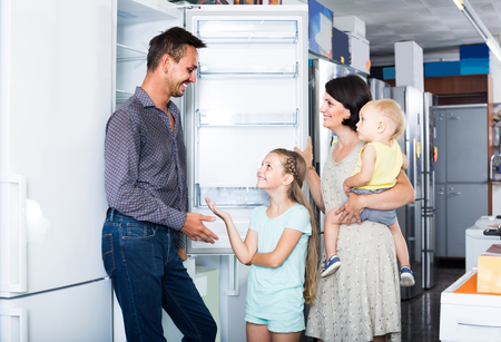 positive family of four shopping new refrigerator in home appliance store