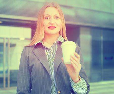 Donna di affari sorridente in vestito con la tazza di caffè nella mano Archivio Fotografico