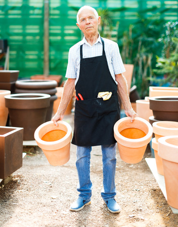Elderly amateur gardener looking for pots for growing plants at his smallholding