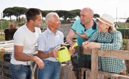 Family of four gardeners talking together near wooden fence in garden outdoor