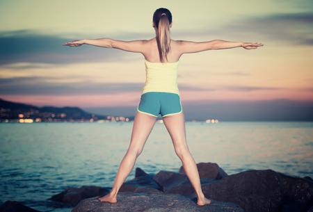 glückliche tschechische Frau in Sportkleidung, die Übungen bei Sonnenuntergang am Meer macht Standard-Bild