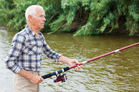 Cheerful adult fisherman standing with angling rod and fishing at sunny summer day