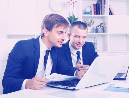 two friendly smiling business male assistants wearing formalwear working together using laptops in company office Imagens