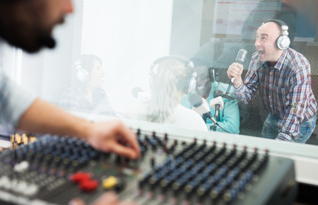 Expressive adult man singing during live radio show in studio. View from sound engineer room