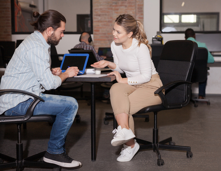 Positive European girl and Hispanic young man developing business strategy, talking at office desk in coworking space