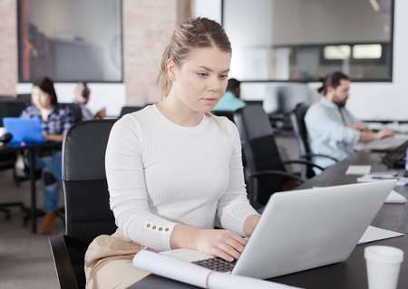 Focused young female working with laptop in busy modern open plan office Imagens
