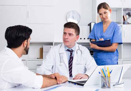 Experienced man physician in lab coat consulting male in medical office Stockfoto