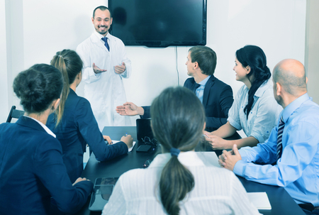 Positive smiling scientist presenting report during working meeting in office