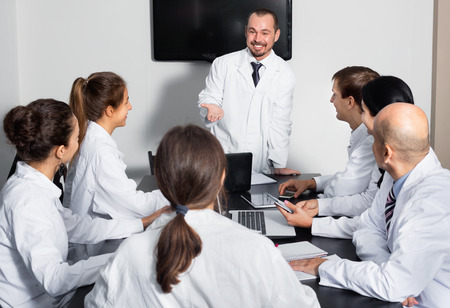 Positive scientist presenting report during working meeting in office