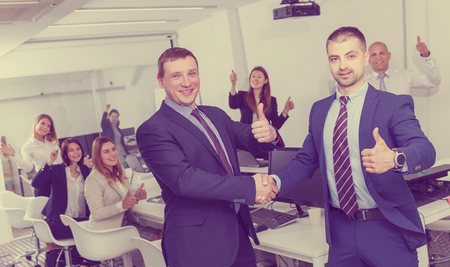 Two young satisfied businessmen shaking hands while finishing up meeting, making agreement