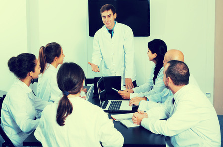 Adult specialists in white overalls having discussion of research work Фото со стока