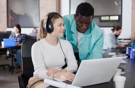 Confident African man explaining business project for young woman in modern coworking space pointing at laptop screen