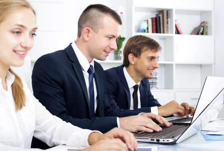 Portrait of cheerful business man sitting with laptop on desk in office with work fellows Imagens