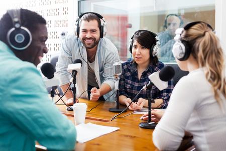 Lächelndes internationales Team von Radiomoderatoren, die mit Gästen im Studio diskutieren