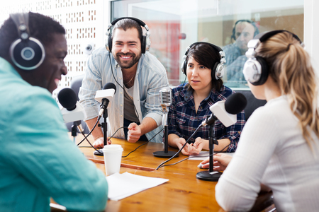 Smiling international team of radio hosts discussing with guests in studio