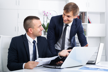 two positive smiling male business colleagues in formalwear working together using laptops in company office