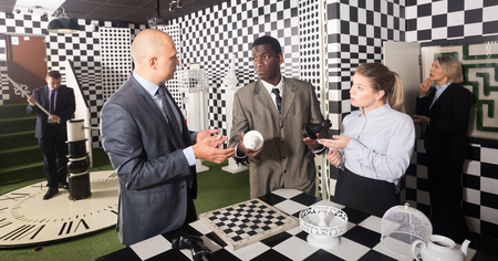 Men and women in business suits solving puzzles with chess to get out of escape room