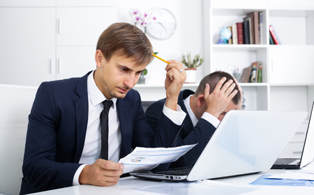 Two sad males coworkers experiencing business failure in firm office