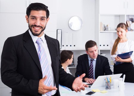 Lächelnder Geschäftsmann mit professionellem Geschäftsteam hinter während der gemeinsamen Arbeit Standard-Bild