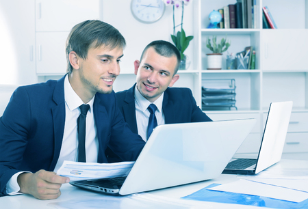 two smiling men coworkers working on computers and with documents in firm office Imagens
