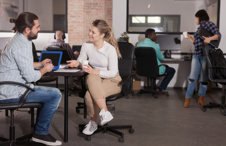 Young bearded man sharing business ideas with his female colleague in open plan office. Concept of teamwork